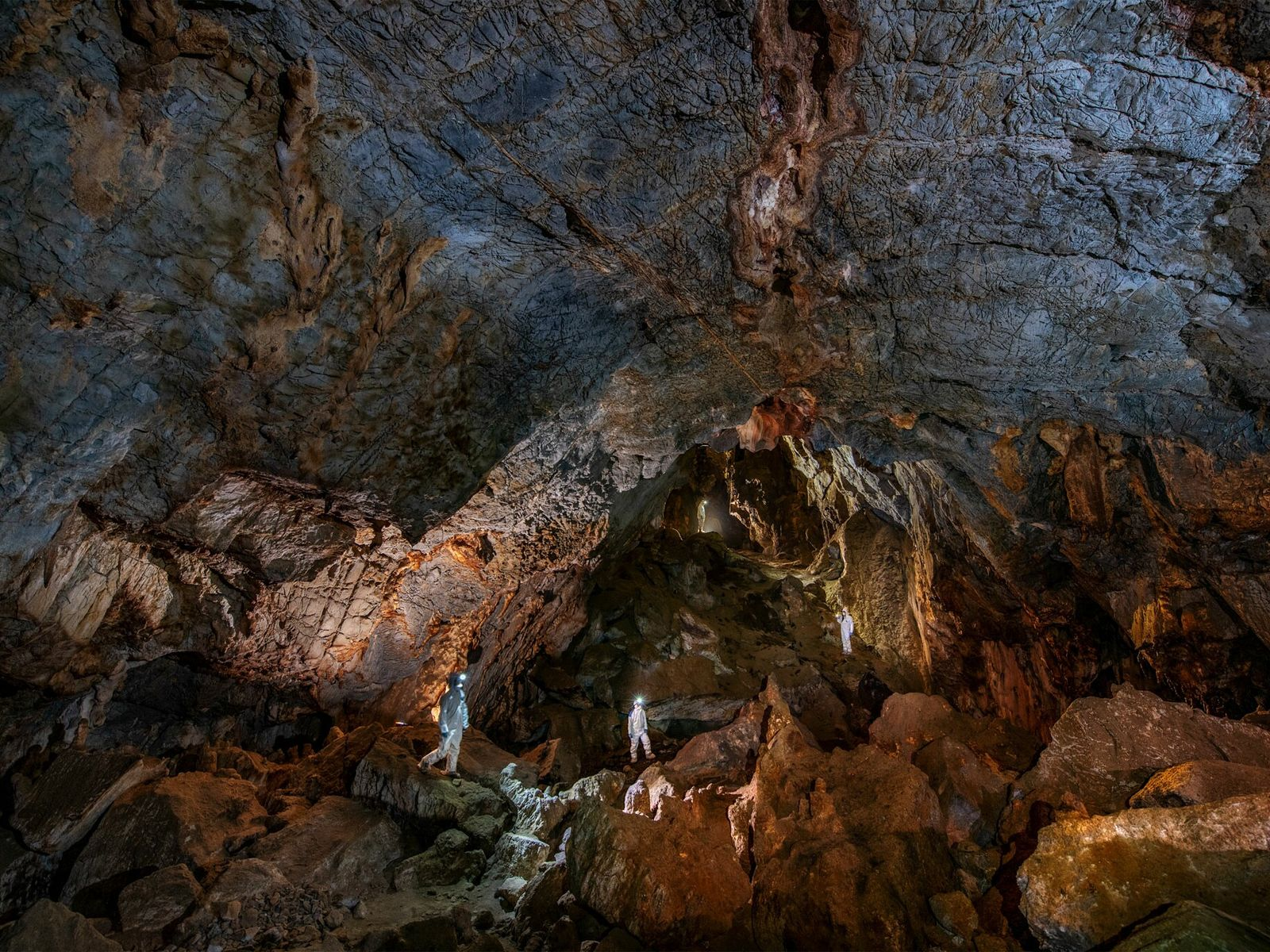 Researchers in Chiquihuite Cave wear protective gear to prevent contamination of excavation areas where they are ...