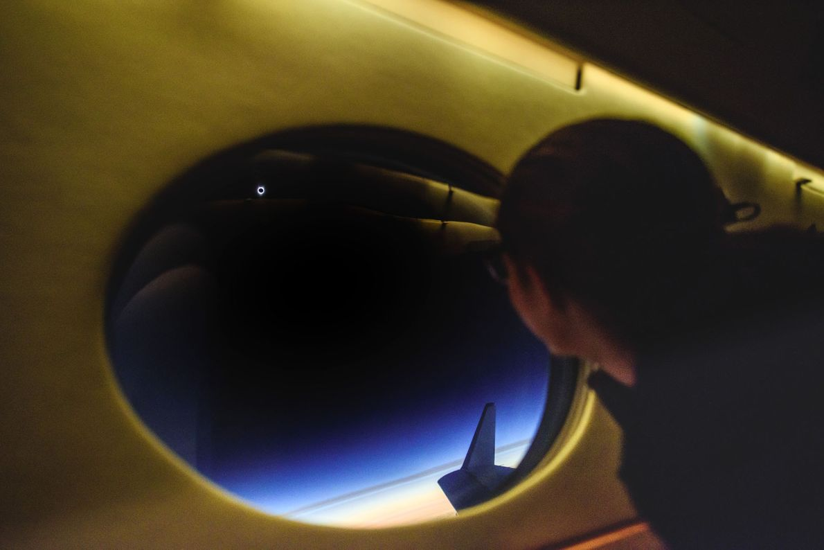 Aboard the plane following the eclipse's shadow, Tafreshi captures a passenger peering at the pale ring ...