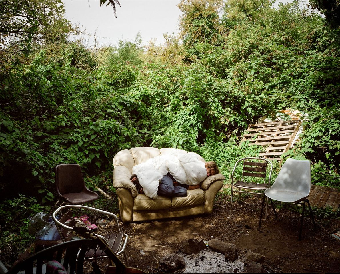 A person sleeps on a couch at the Grow Heathrow site. Visitors come to to the ...