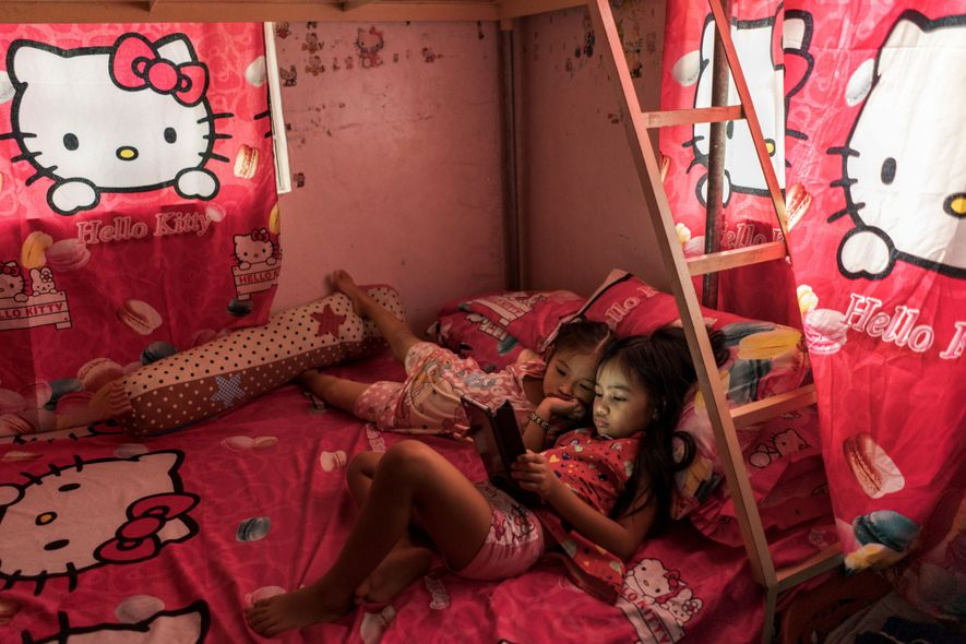 Althea Tolidanes, eight, watches videos amid gifts of sheets, pillows, and curtains from her father, who ...