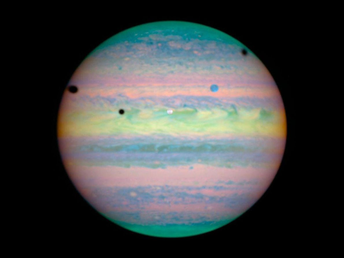 Seen in infrared by the Hubble Space Telescope, the three large moons Io, Ganymede, and Callisto ...