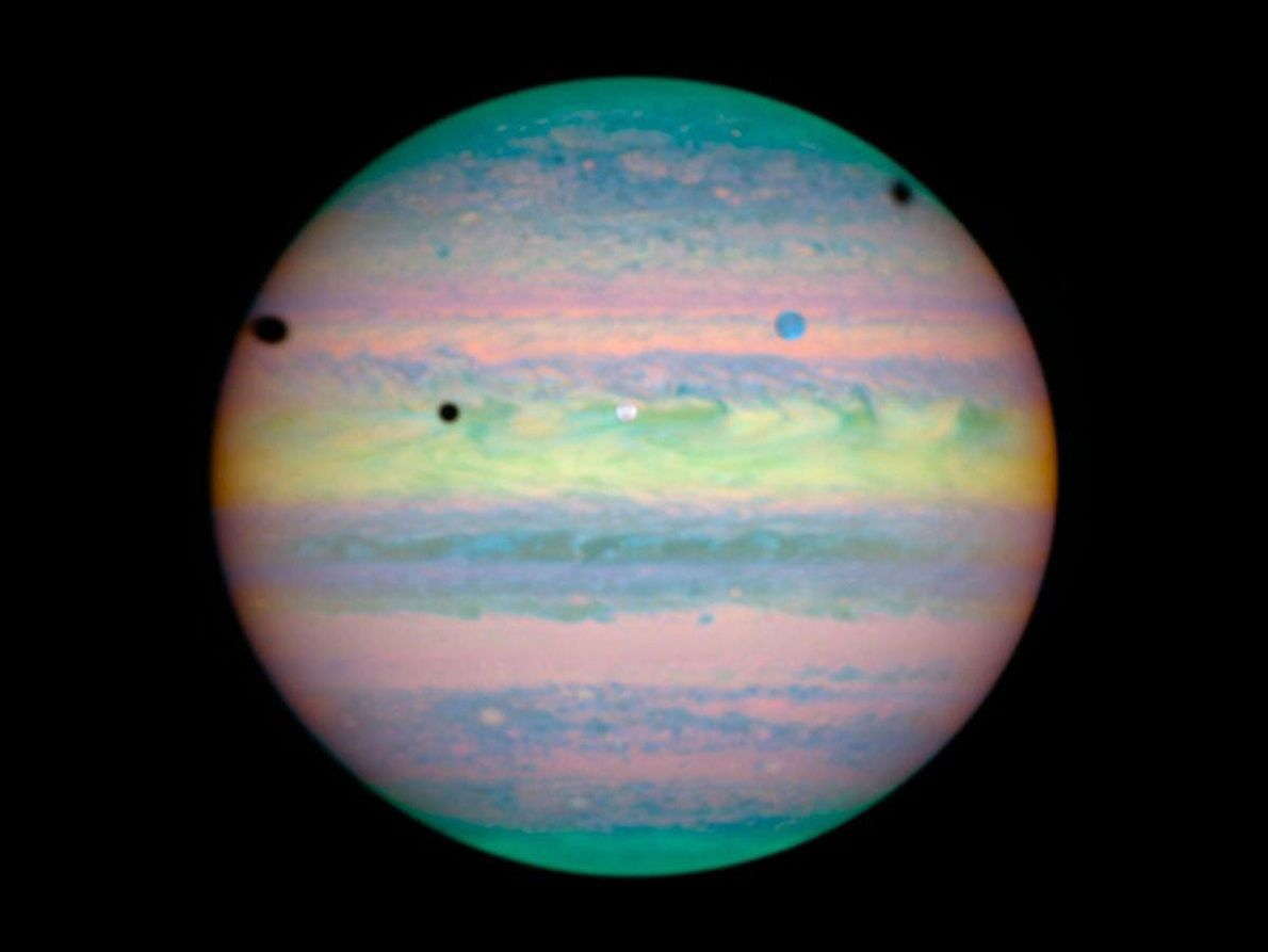 Seen in infrared by the Hubble Space Telescope, the three large moons Io, Ganymede, and Callisto …