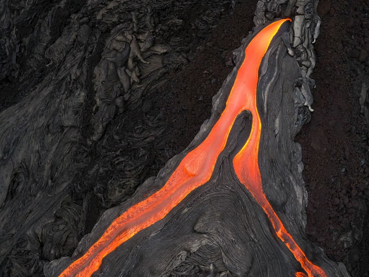 The flows diverge into two streams and run down the mountain in this drone shot.