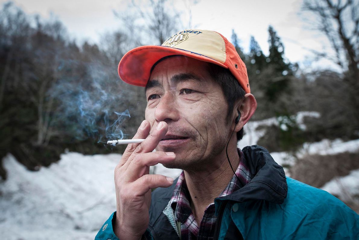 A Matagi hunter smokes at the foot of the mountain after having successfully completed the hunt.