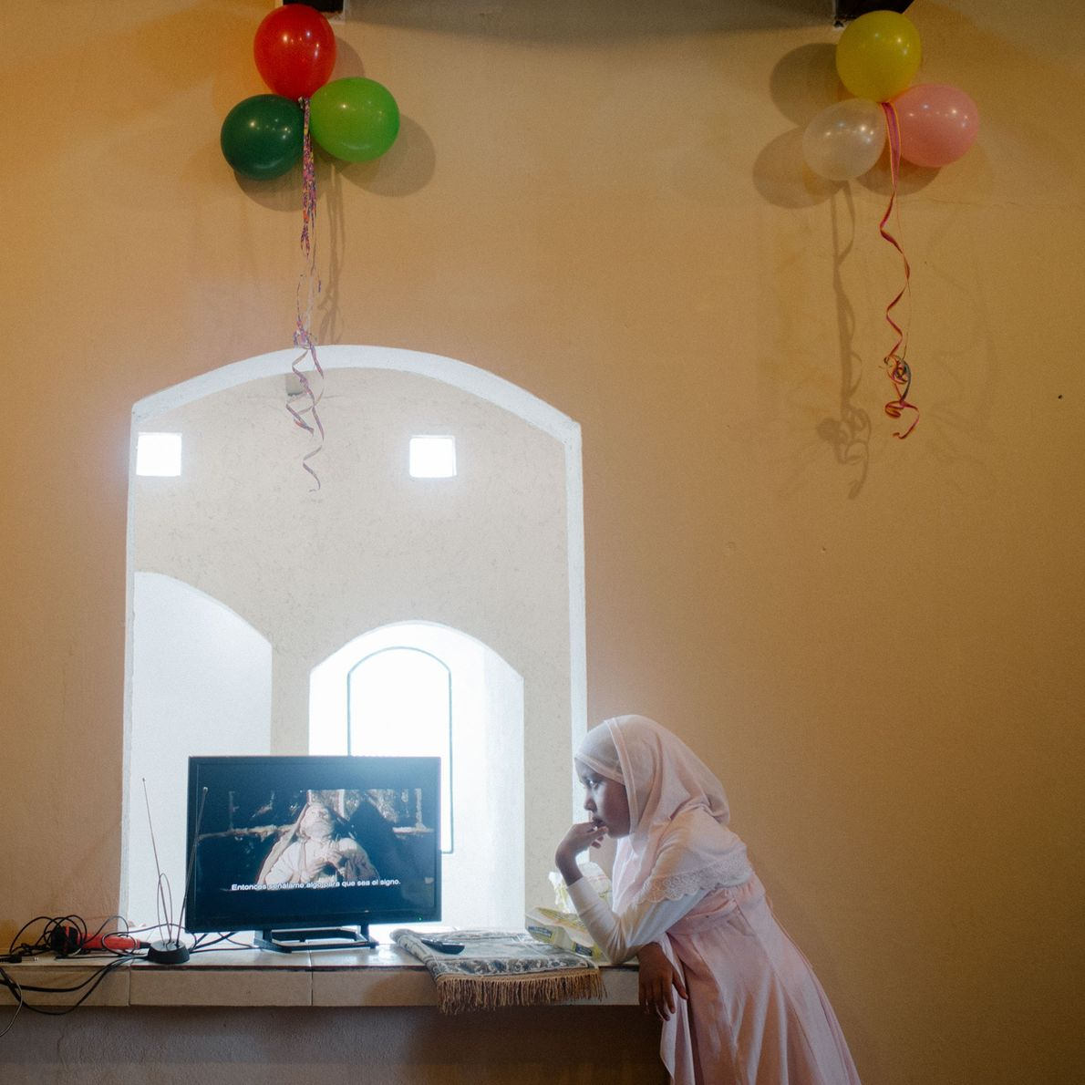 Eleven-year-old Ramka watches a movie about the Virgin Mary during the holy feast of Eid al-Adha.