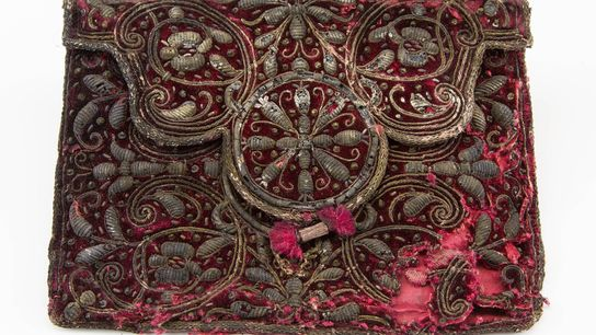 This red velvet pouch is embroidered with silver thread and was found with a comb inside. ...