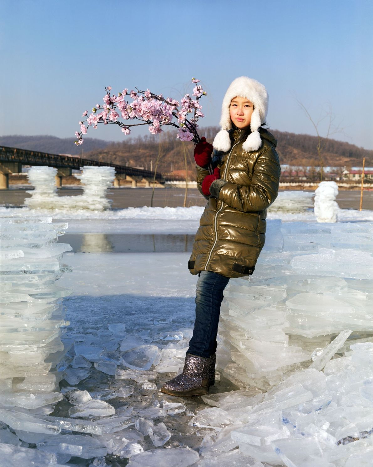 Yuting, 10, stands on the bank of the Hun River with a bouquet of artificial flowers ...