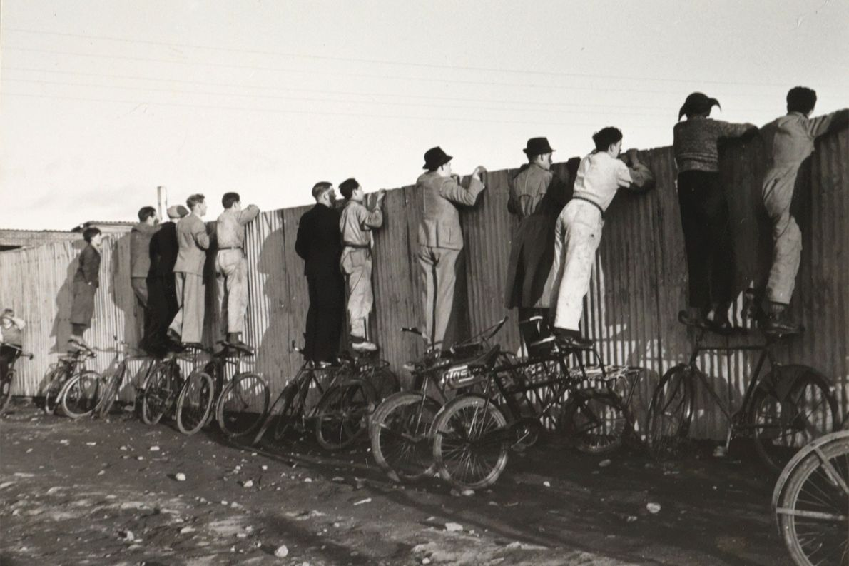 Balancing on bicycles, Icelanders peer over a fence to watch football in Iceland in 1943.  ...