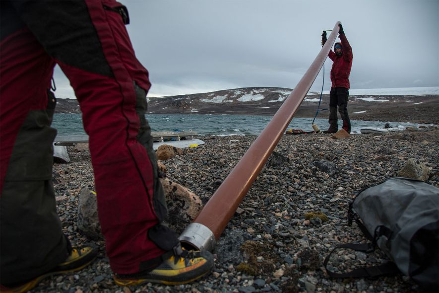 The team of scientists prepares a tube for the coring of lake sediments on the shore ...