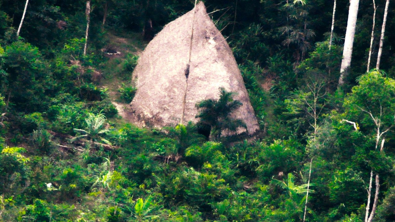 A communal dwelling, or maloca, of the Flecheiros, or Arrow People, photographed from a drone on ...