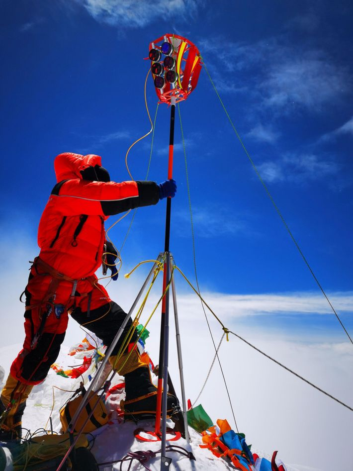 A member of a Chinese survey team sets up a marker on the summit of Mount ...