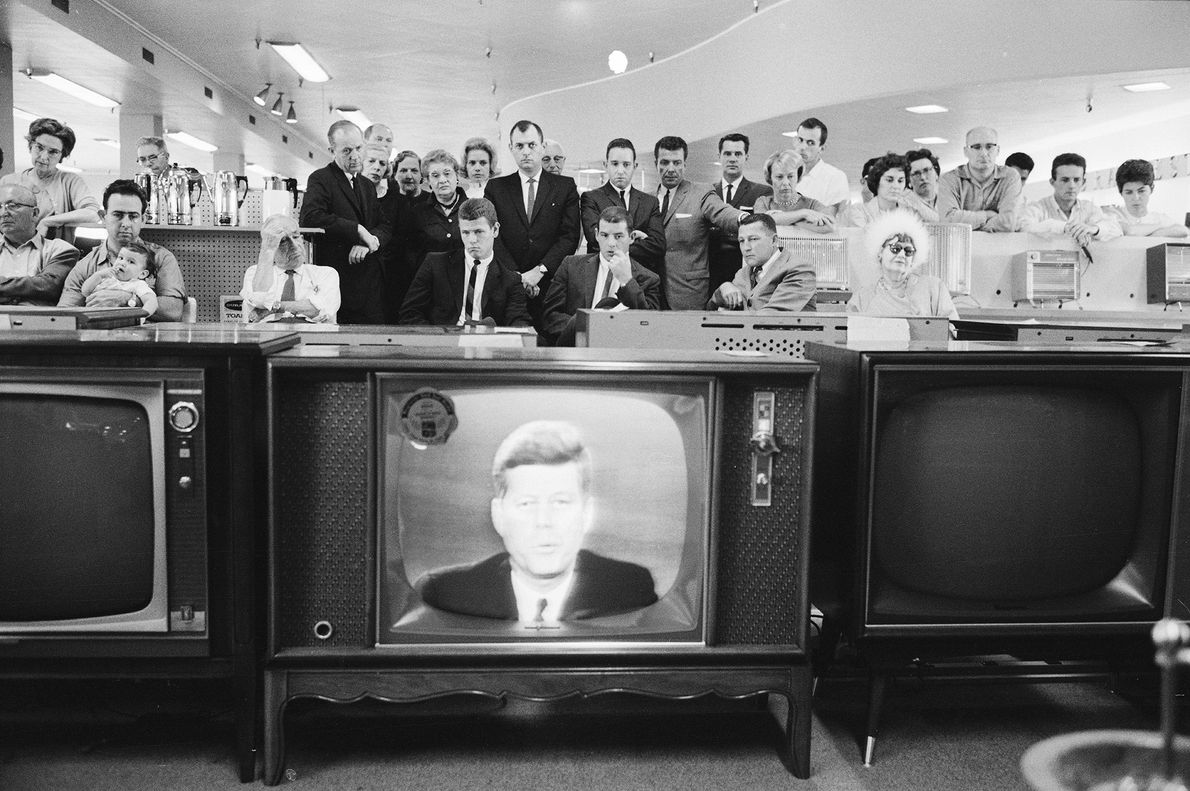 A large group of customers in an unidentified store gather in the electronics department to watch ...