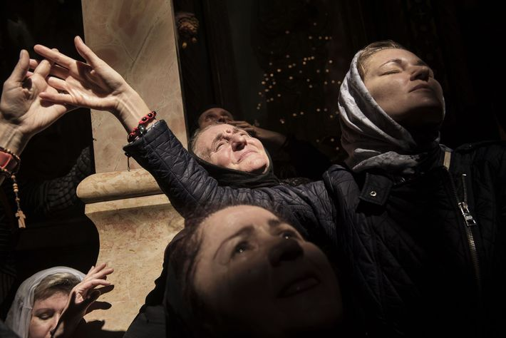 Orthodox pilgrims stand in the light coming from the window of the Holy Sepulchre.