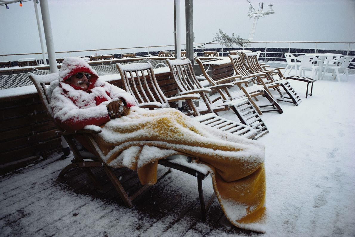 A dedicated Antarctic tourist sleeps on a deckchair during snowfall close to the Amundsen Sea.