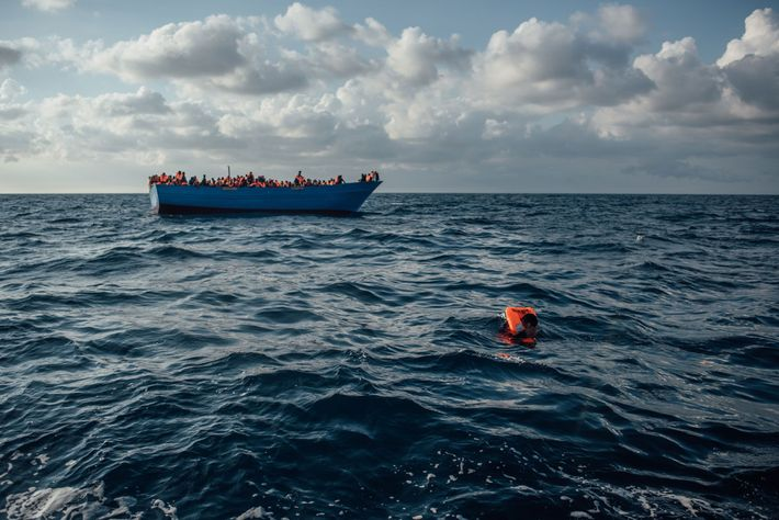 Rescue workers in a small RHIB provide life jackets to refugees in advance of their rescue, ...