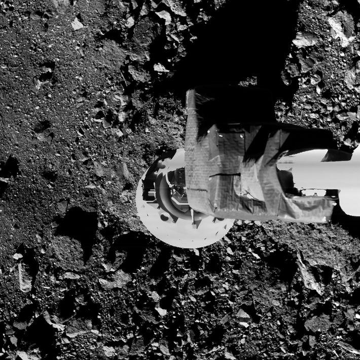 In a practice run, the OSIRIS-REx spacecraft's sampling arm drops close to Bennu's surface. The goal ...