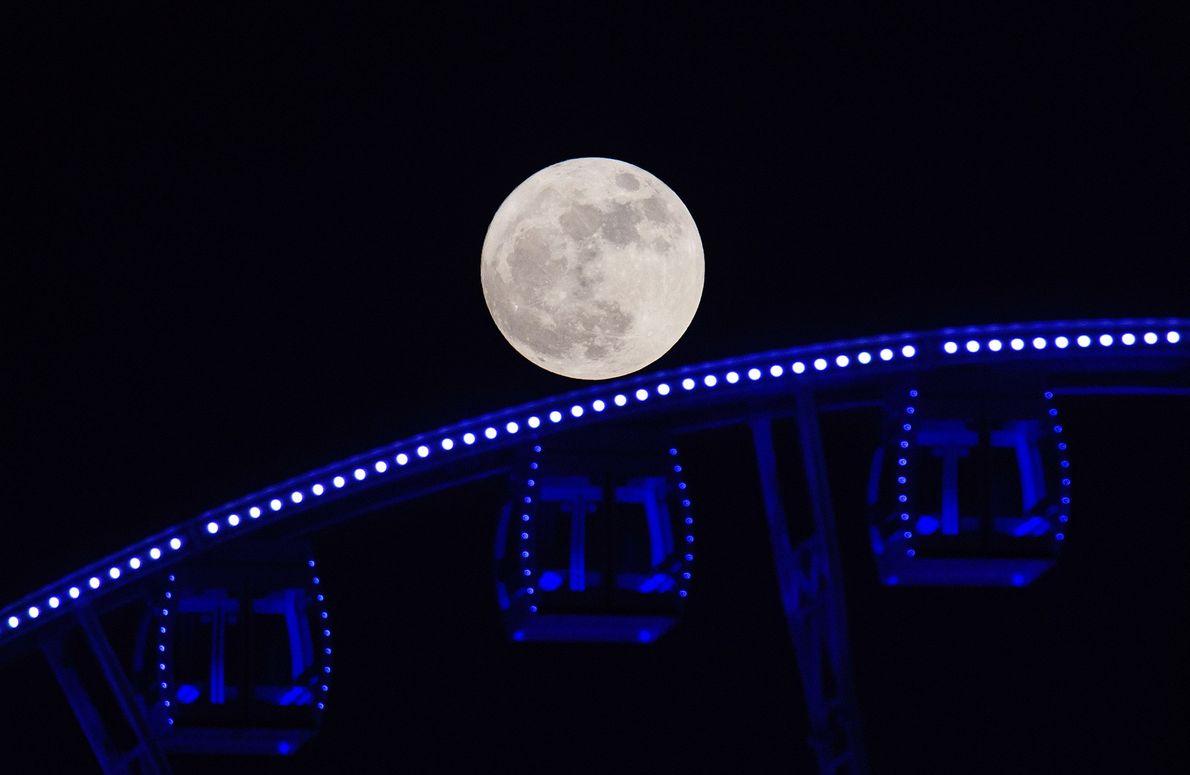 The November 2016 supermoon looms over a ferris wheel in Hong Kong.