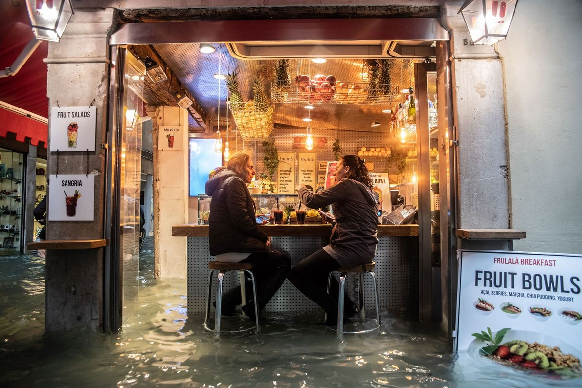 Locals pause for a drink despite the high water.
