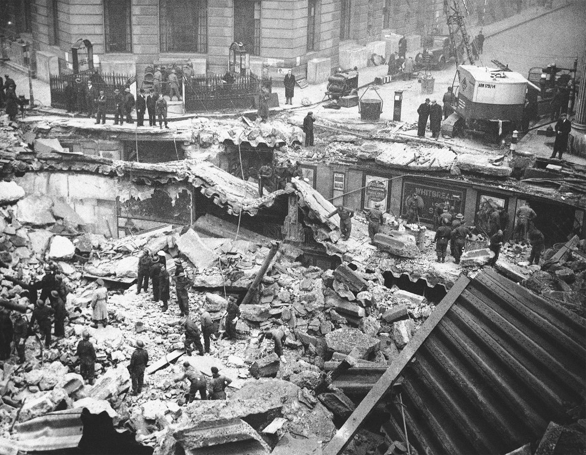 Workmen search for bodies in the wreckage of London after German bombing raids.