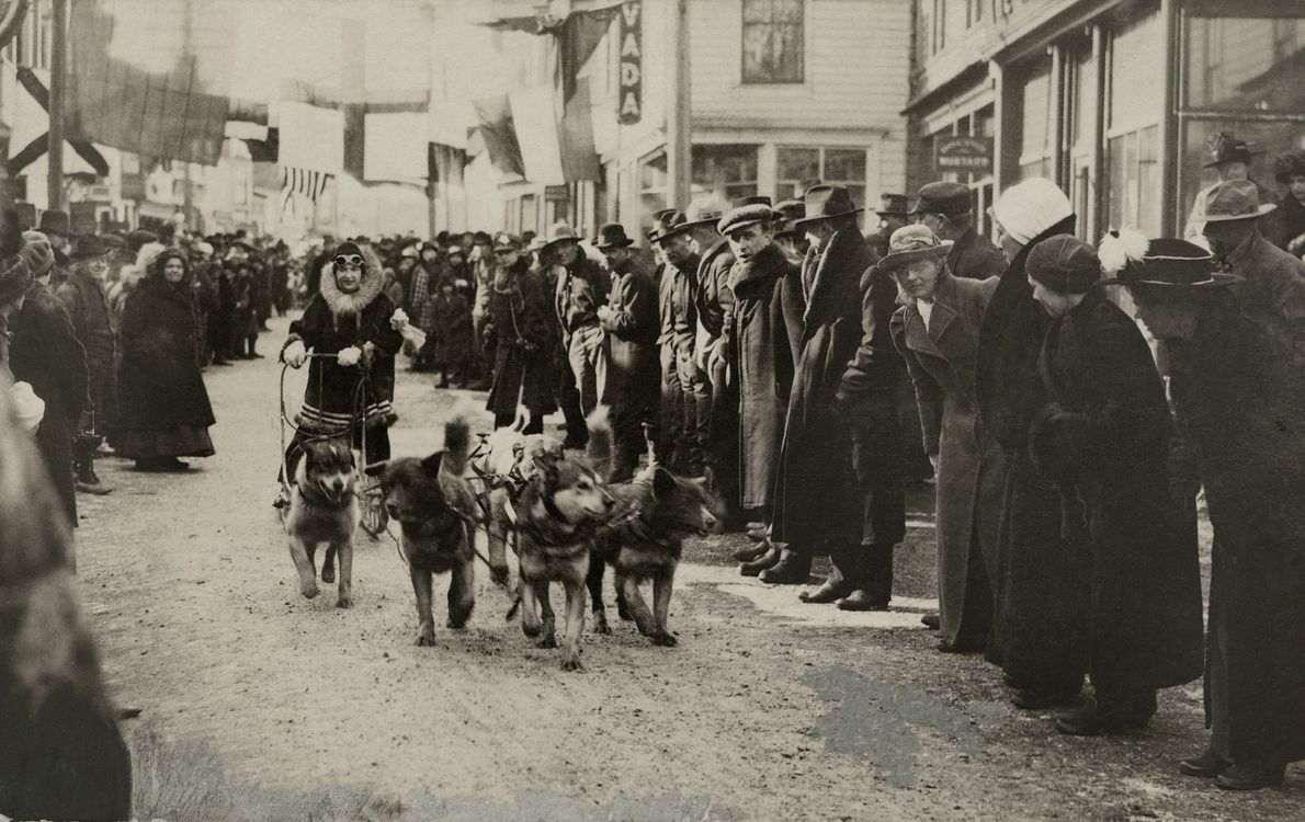 A woman drives her team through Nome, Alaska, in this photo from a 1919 issue of ...