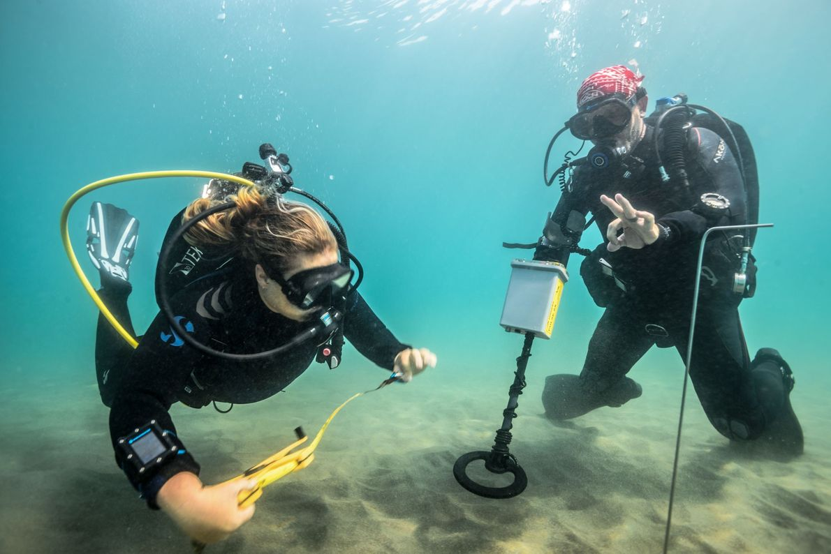 Project archaeologists prepare to search the seafloor with a magnetometer, which can detect buried metallic objects ...