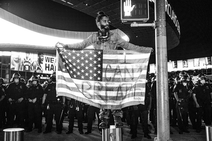 """A man calling himself """"Royal G"""" stands above a phalanx of police officers at a protest. ..."""