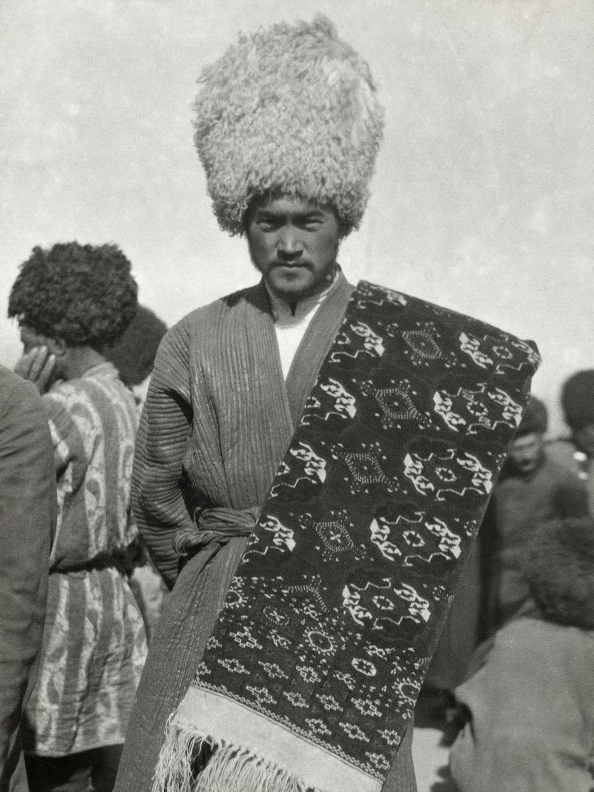 A rug dealer from Turkmenistan in the early 1900s wears a wool telpek hat. The rug ...