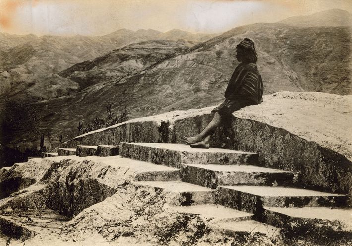 A Peruvian local sits atop the Incan fortress of Saqsayhuamán overlooking Cusco, Peru.