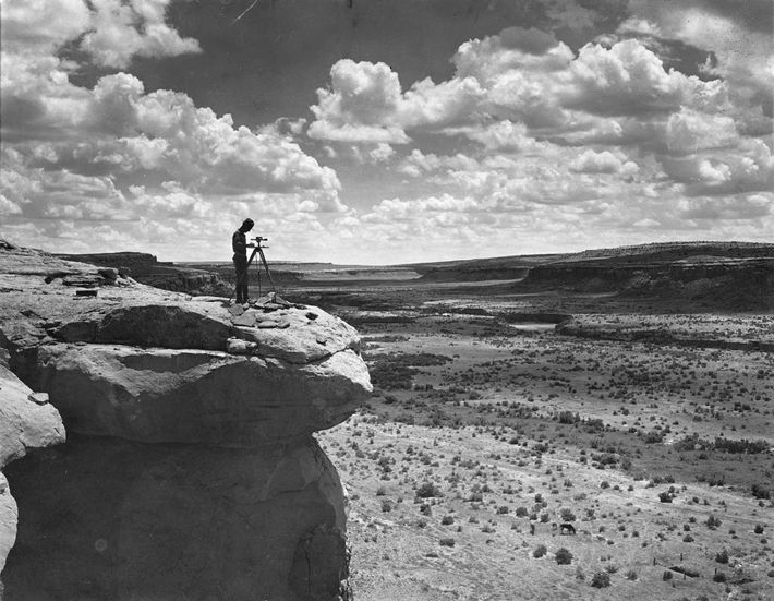 A surveyor maps Chaco Canyon while standing on a cliff.