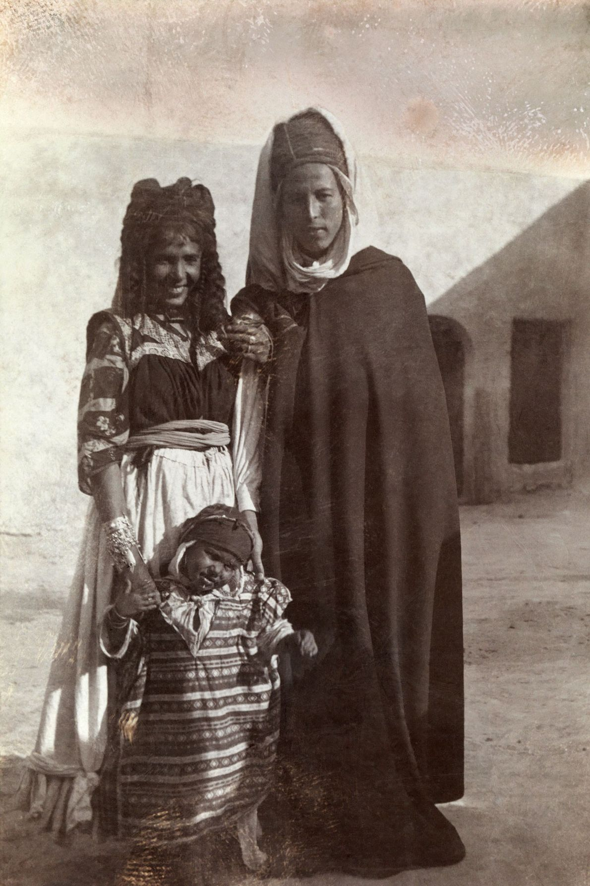 A young Algerian couple in Biskra stand with their toddler in front of a building.
