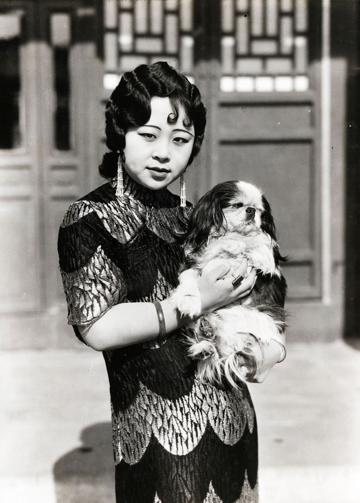 A stylish Manchu princess who married a Mongol prince clutches her dog in Beijing in 1932.