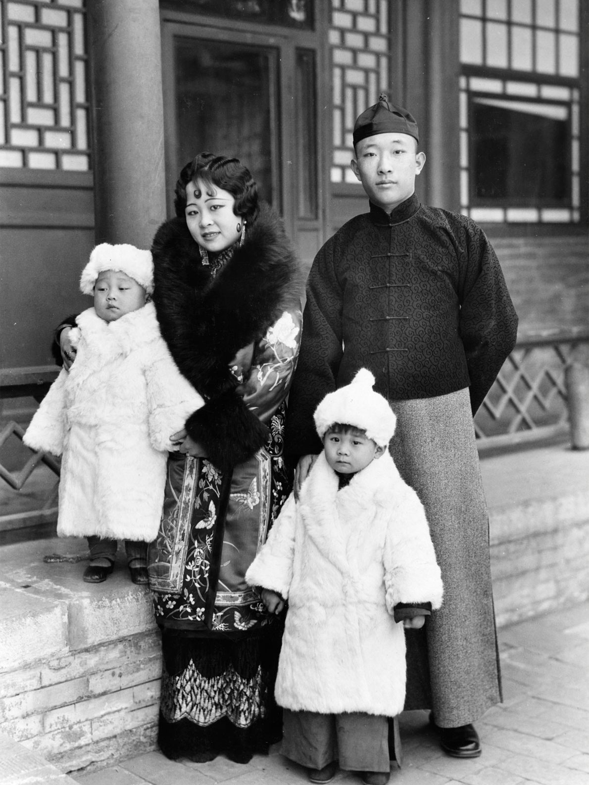 A Mongol prince and princess stand with their young children, wrapped in warm furs to ward ...