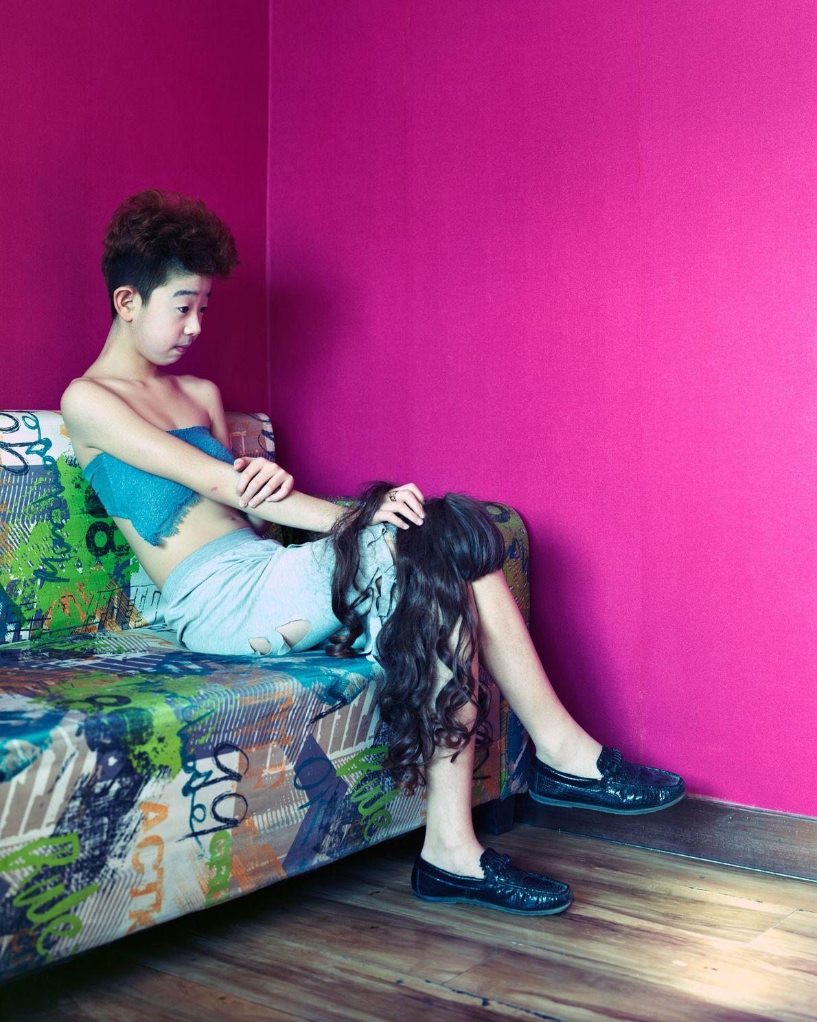 Lin Zi, 14, sits in a café where internet celebrities live stream performances online in Fularji. ...