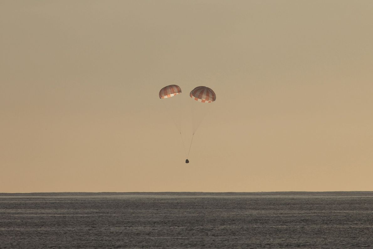 A Dragon spacecraft parachutes toward the Pacific Ocean after completing a supply run to the ISS ...