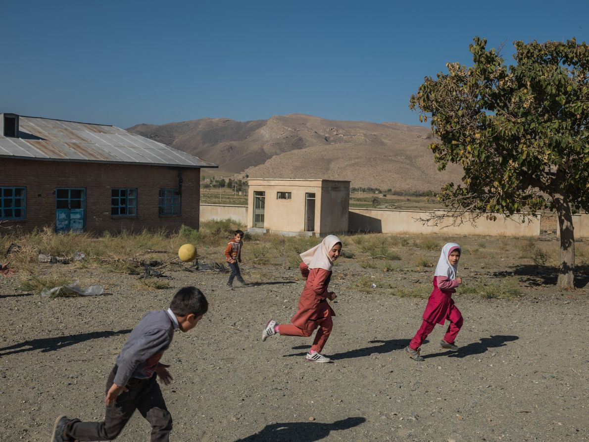 Students run around at Qalqachi primary school's playground. There are eight students left in this school. ...