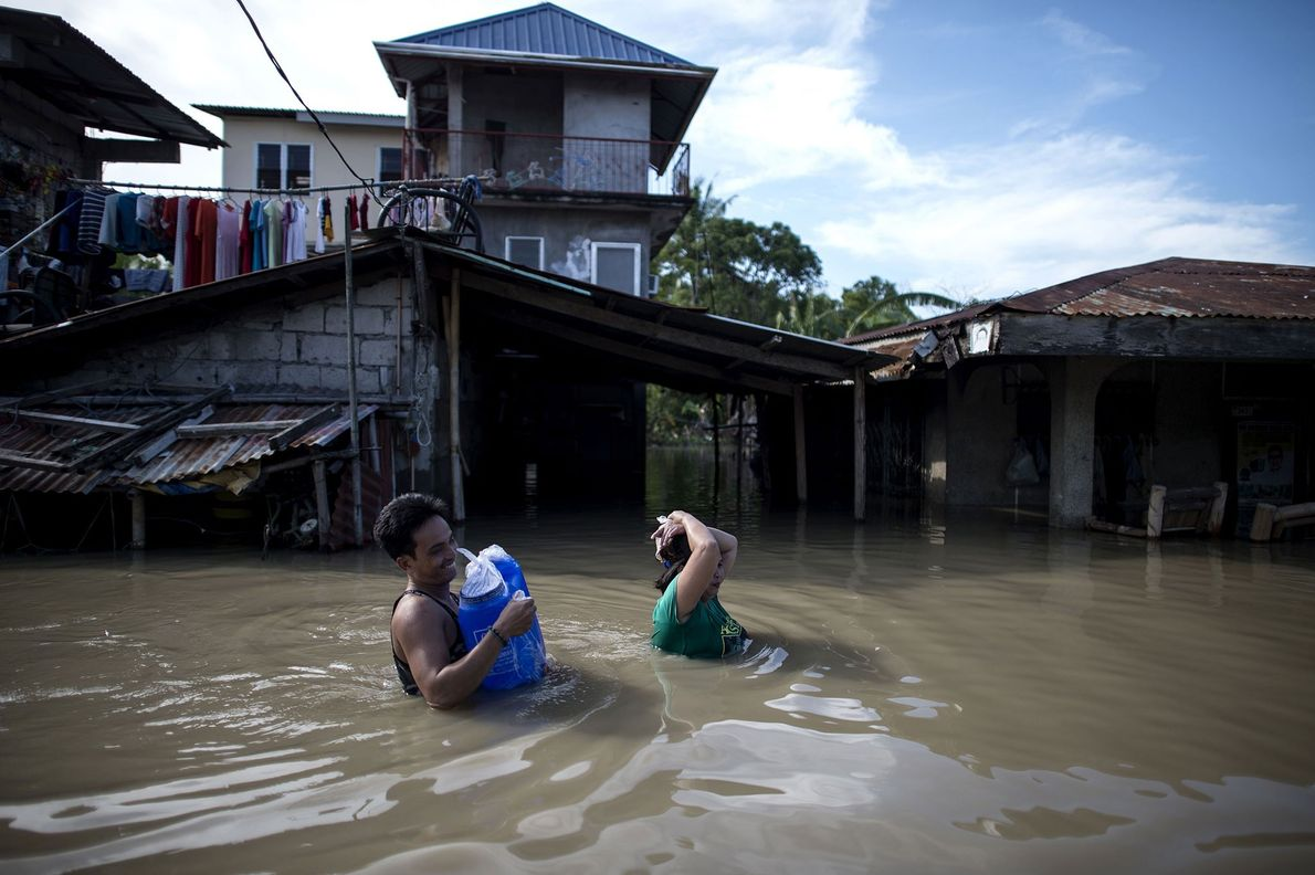 Residents wade through the flooded streets of Calumpit, Bulacan in the Philippines. Here, damaging floods created ...