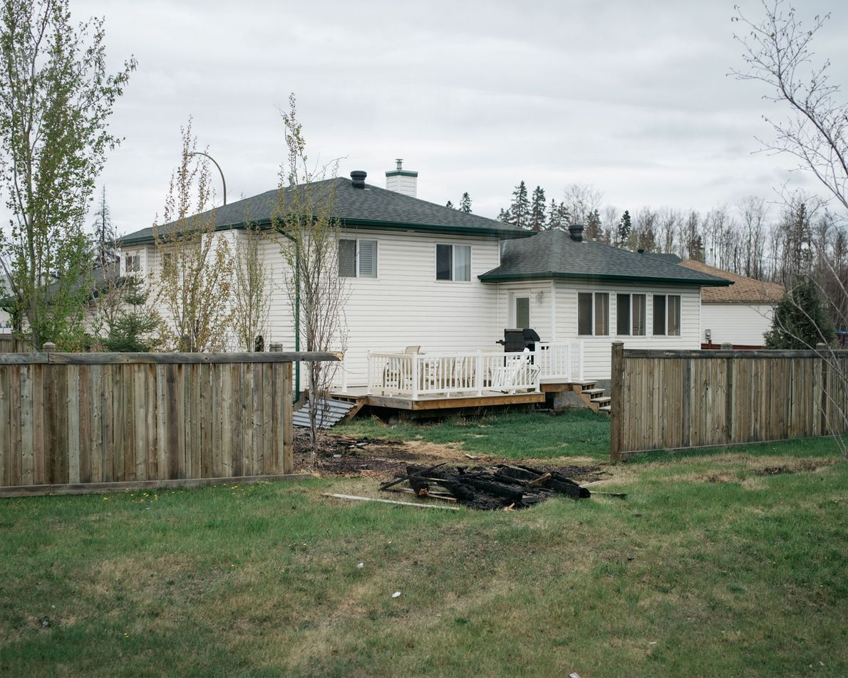 As it passed, the fire destroyed a section of fence, but left the home behind it ...
