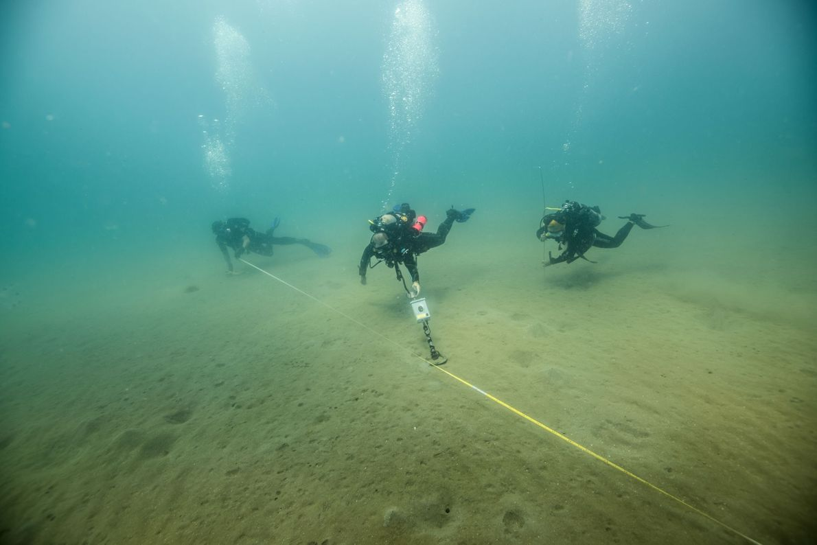 Archaeologists perform a magnetometer survey under the waters of the Gulf of Mexico. A tape measure ...