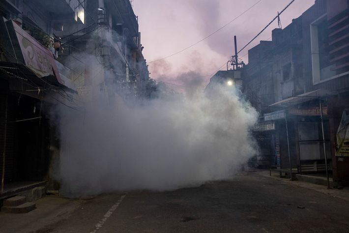 Before a sample collection team arrives, a hotspot area in Lucknow, India is sprayed with disinfectant ...