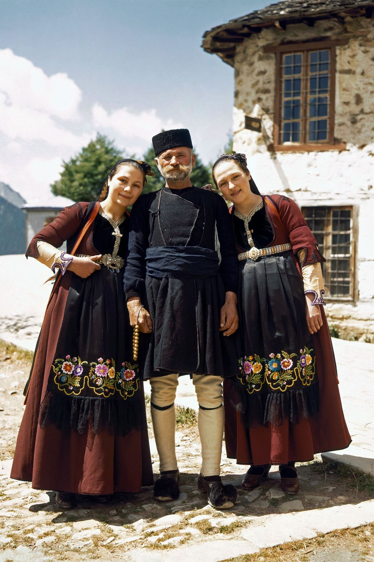 Two daughters in traditional clothing stand next to their father, a shepherd, in Metsovo, Greece.