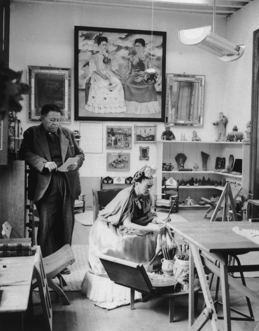 Married Mexican artists Diego Rivera and Frida Kahlo read and work in a studio. Kahlo's self-portrait, ...