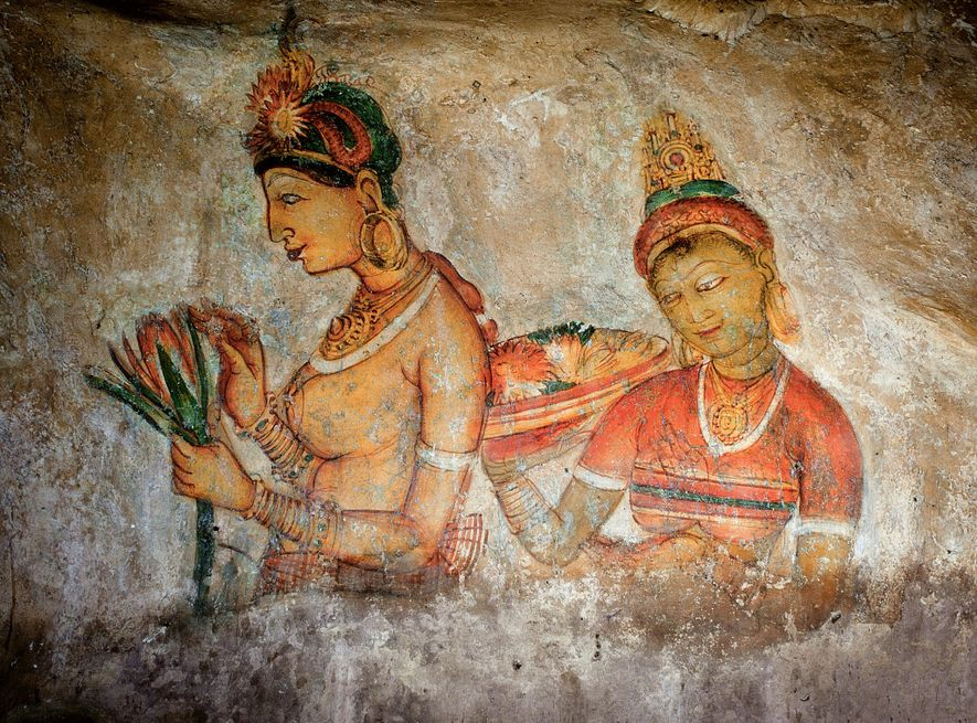 """Graffiti left by medieval travelers to Sigiriya are responses to the site's extraordinary rock paintings depicting beautiful women dancing and bearing offerings. One notes: """"The caress of the gentle breeze was delicate upon their bodies, illuminated by the light of the moon's rays."""" Historians have differed as to the identity of the women represented high up on the cliff wall. Their solid and sensual forms have led some writers to believe they are depictions of women from Kashyapa's harem. Another theory believes them to be depictions of apsaras, singers and dancers in Indian mythology who inhabit heaven."""