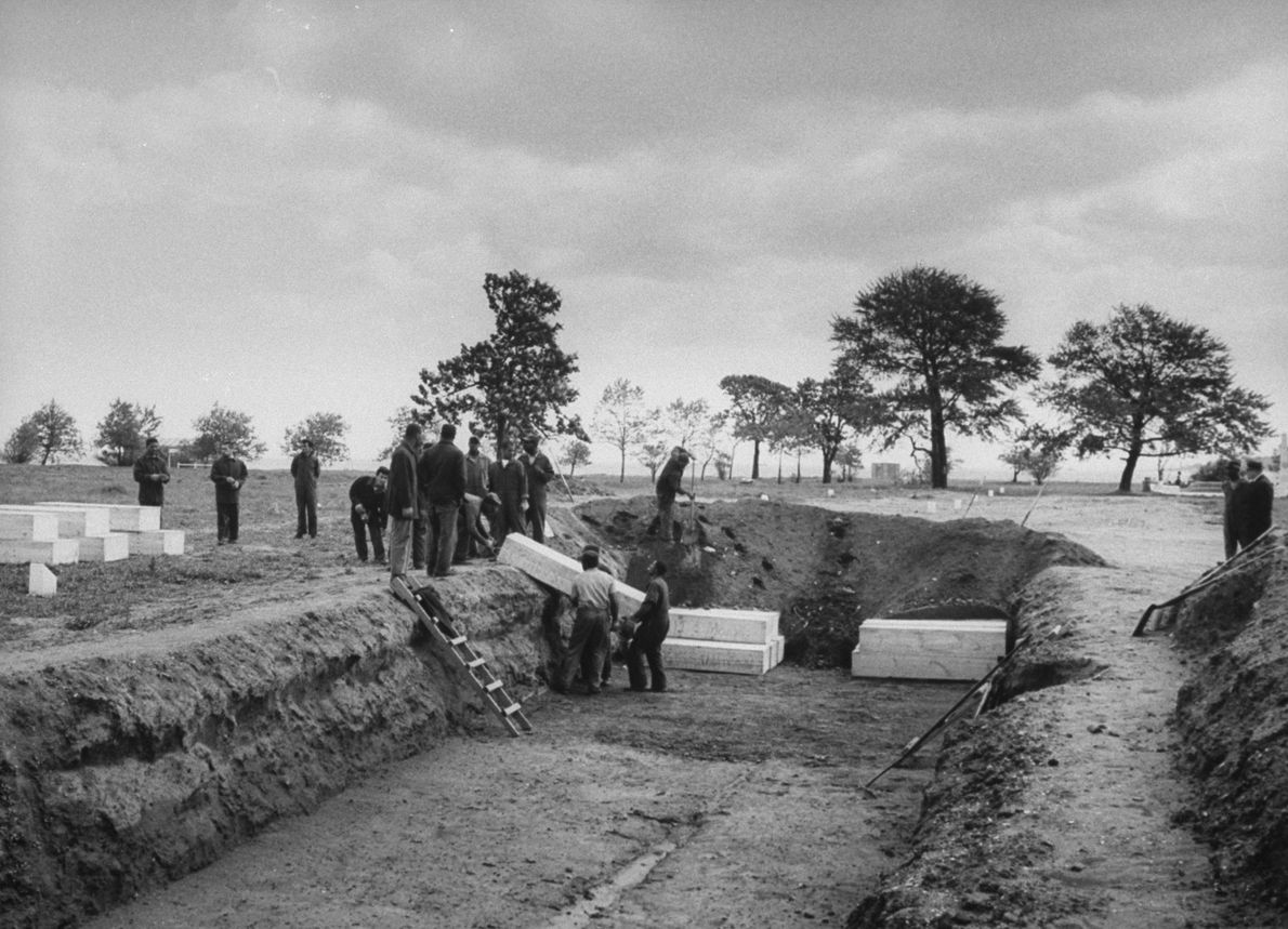 Prisoners in 1963 bury the bodies of men who were poisoned by drinking wood alcohol, also ...