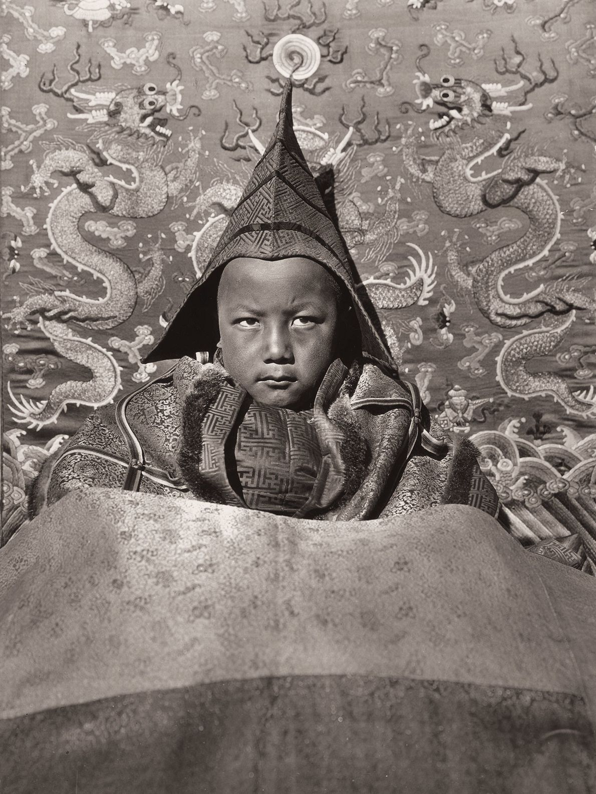 The young Living Buddha of Guya, ruler of a monastery at the age of six, wears ...