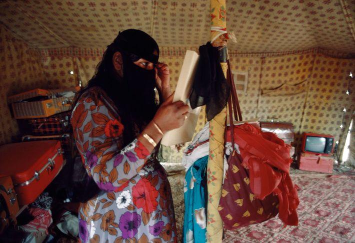 A Bedouin woman adjusts her veil in a tent at Wadi Nisah in Saudi Arabia.
