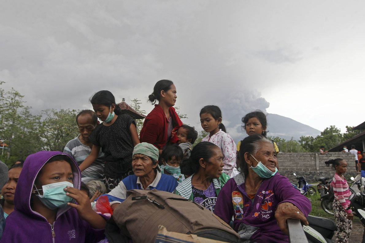 Villagers sit on a truck to evacuate the region surrounding Mount Agung.