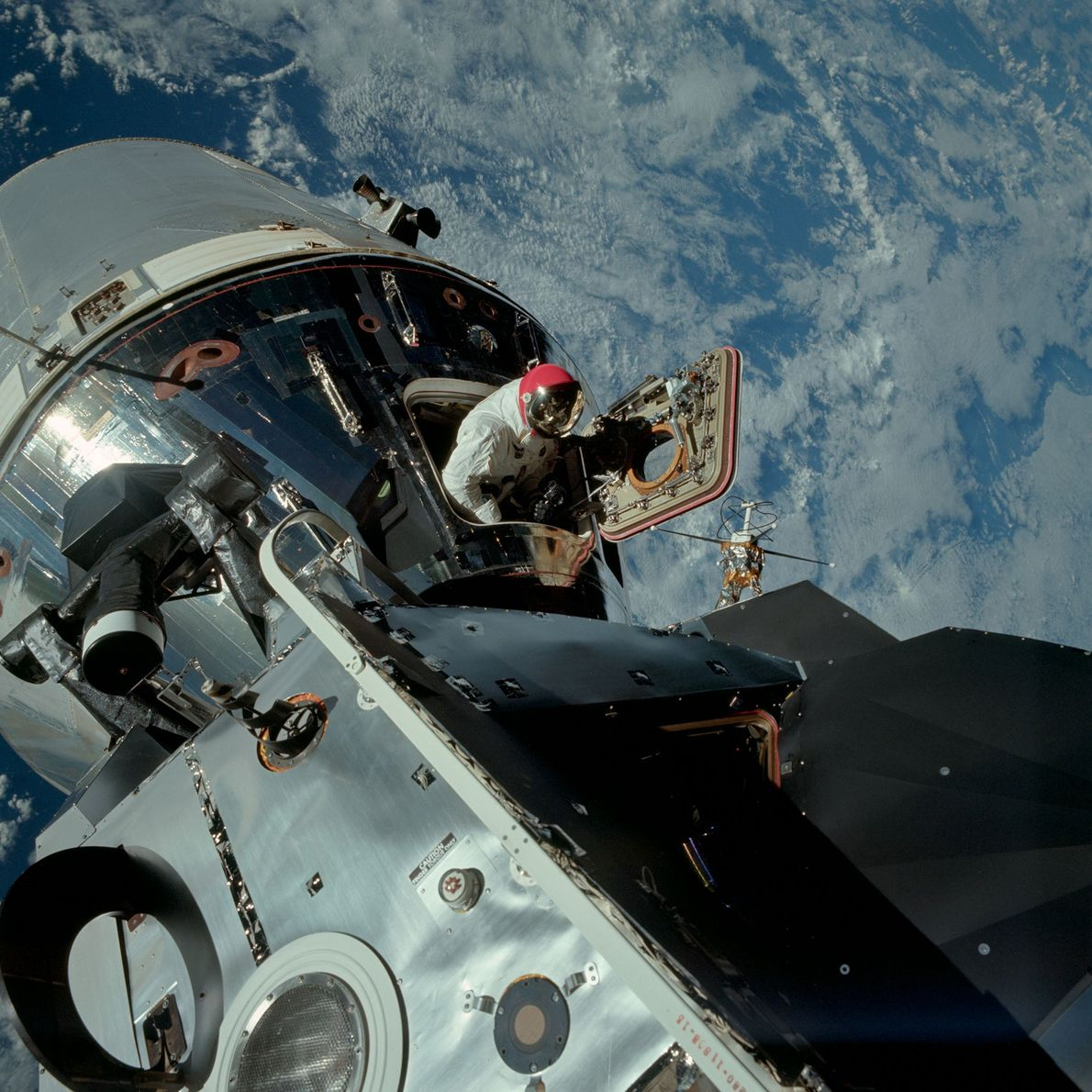 Astronaut Dave Scott pokes his head out of the Apollo 9 command module while it orbits ...