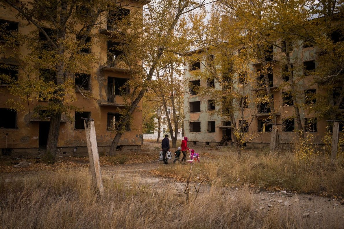A family passes derelict housing blocks in the town of Kurchatov, Kazakhstan. The population of the ...