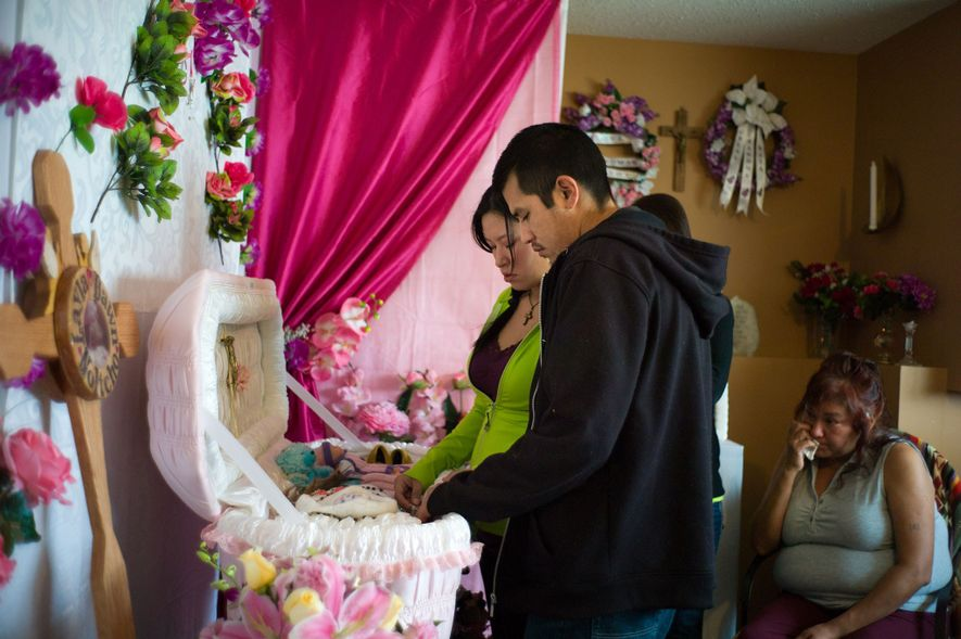 Wade and Chelsea (at center) say goodbye to their infant daughter during her burial in Fort ...