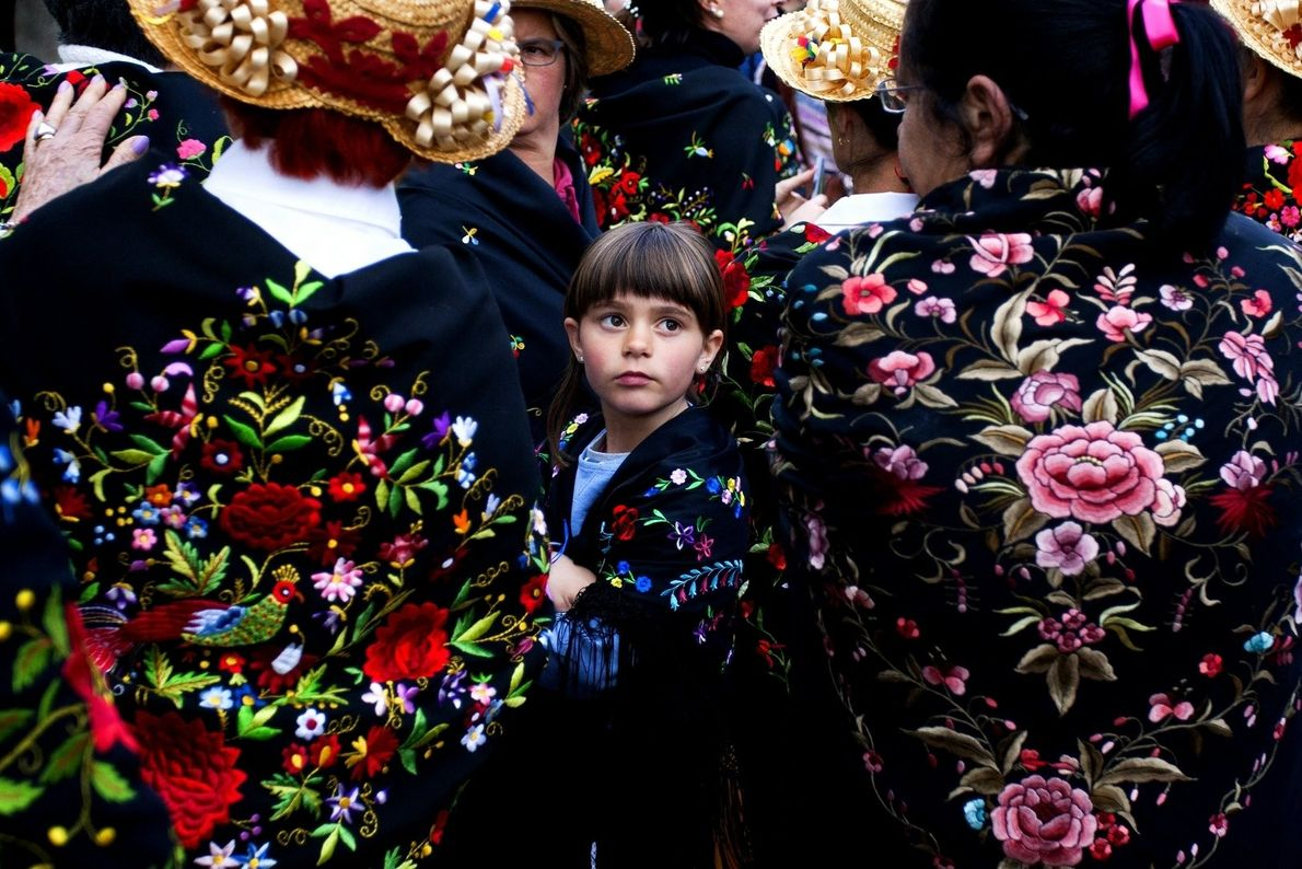 """""""A girl stands among several women dressed in traditional costume at a masquerade festival held in ..."""